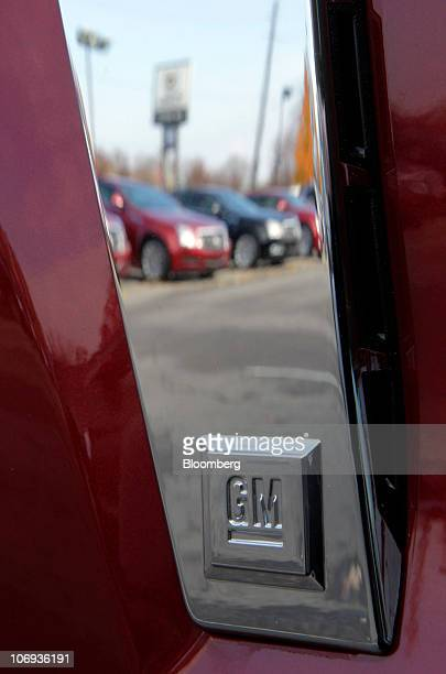 Cars are reflected in the trim of a General Motors Co. Cadillac SRX at the Don Massey Cadillac dealership in Plymouth, Michigan, U.S., on Wednesday,...