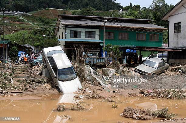 Cars are seen along the riverside after water was released from a dam in Malaysia's Cameron Highlands on October 23 2013 Water released from a dam...