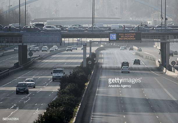 Cars are seen on a motorway as a sign displays 'High Level Air Pollution' alert in Madrid Spain on December 25 2015 Traffic will be restricted to 70...