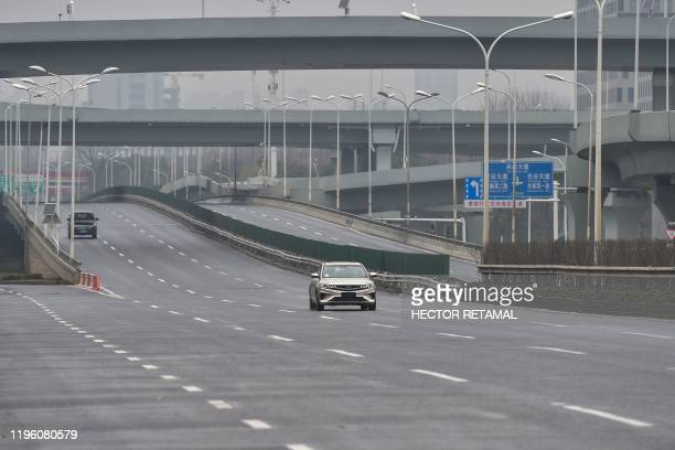 Cars are seen on a road on the first day of the Lunar New Year in Wuhan in China's central Hubei province on January 25 during a deadly virus...