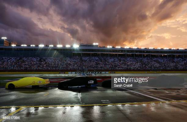 Cars are seen on the grid as the sun sets after a rain storm during the Monster Energy NASCAR Cup Series CocaCola 600 at Charlotte Motor Speedway on...