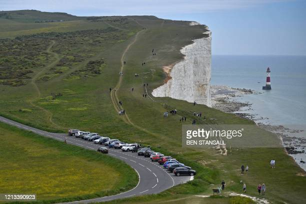 Cars are seen parked beside the road as people walk along the clifftop above the lighthouse at Beachy Head near Eastbourne on the south coast of...