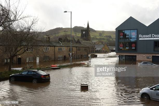 Cars are seen submerged as flood water covers the roads and car parks in Mytholmroyd northern England on February 9 after the River Calder burst its...