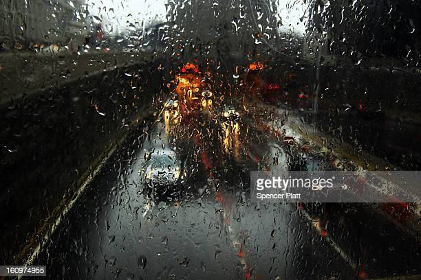 Cars are viewed through a window as they drive in the rain and sleet as Manhattan prepares for a major winter storm on February 8 2013 in New York...