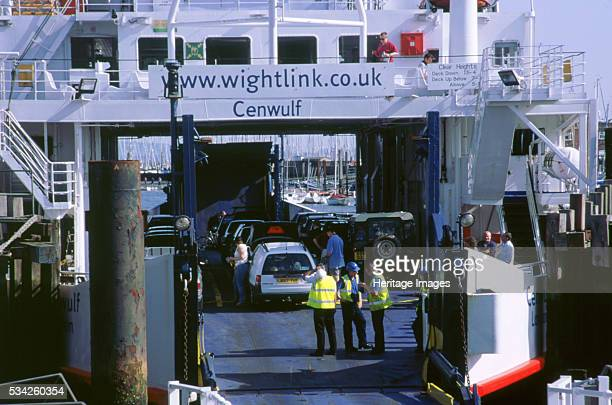 Cars boarding ferry at Lymington bound for Yarmouth Isle of Wight 2000.