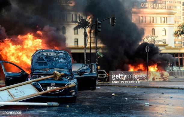 Cars burn in flames outside the O'Higgins Hotel after being set on fire by demonstrators during a protest against Chilean President Sebastian...