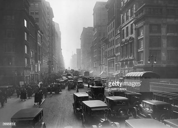 Cars buses and pedestrians crowd the streets and sidewalks of Midtown Manhattan New York City