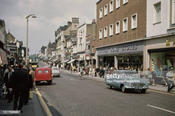 Cars, buses and pedestrians drive and walk along New Road, the main shopping street in the town centre of Gravesend in Kent, England in July 1969....