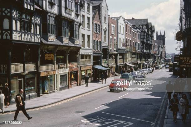 Cars, buses and pedestrians make their way along Bridge Street, a main shopping street in Chester city centre in Cheshire, England in May 1969.