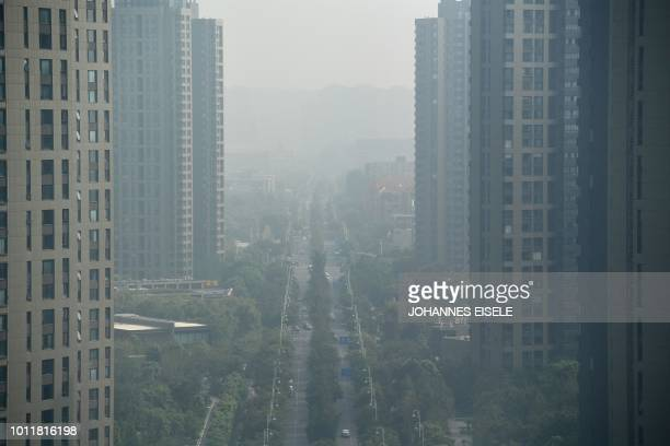 Cars commute along a road on a polluted day in Nanjing, Jiangsu province on August 6, 2018.