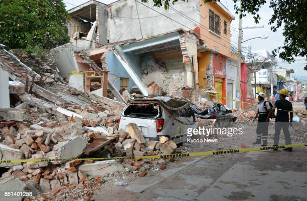 Cars crushed by debris from collapsed houses line a street in this photo taken Sept 21 2017 in Jojutla in the state of Morelos near the epicenter of...
