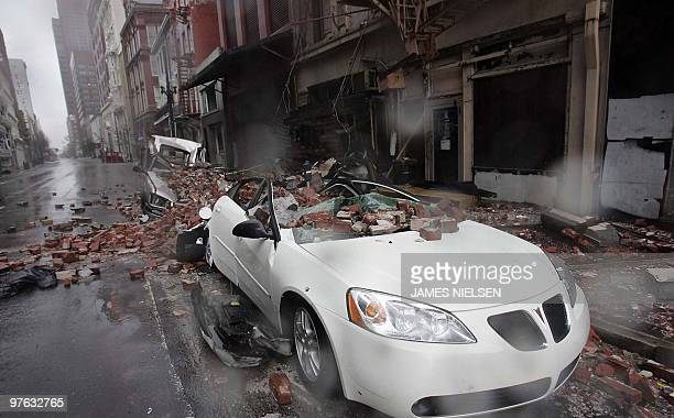 Cars damaged from falling debris stand in the French Quarter of New Orleans 29 August 2005 after Hurricane Katrina made landfall near the Louisiana...