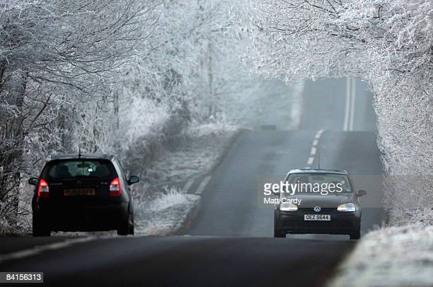 Cars drive along a road as the sun begins to rise near Wells as the recent cold weather continues on January 2 2009 in Wells England According to the...