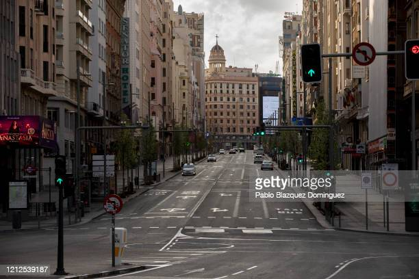 Cars drive along an empty Gran Via Street on March 15, 2020 in Madrid, Spain. The cases in Madrid are 2,807 people infected of Coronavirus and 133...