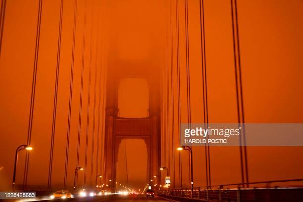 Cars drive along the Golden Gate Bridge under an orange smoke filled sky at midday in San Francisco, California on September 9, 2020. - More than...
