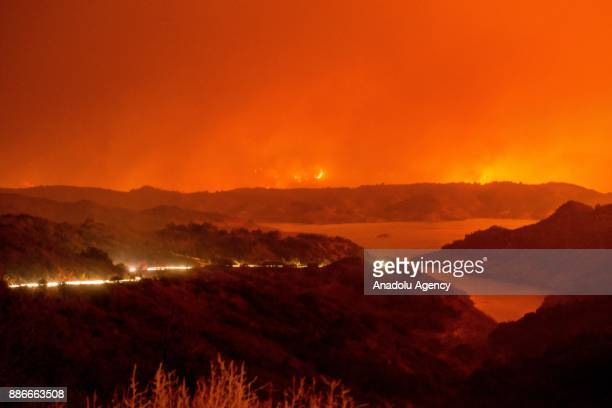 Cars drive around Lake Casitas and away from the Thomas Fire as it crests a mountains near the lake on December 5 2017 in Ventura California United...