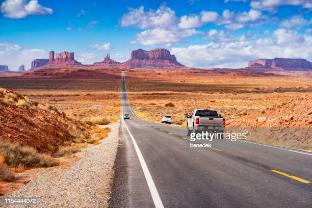 cars drive at forrest gump point in monument valley utah usa - national landmark stock pictures, royalty-free photos & images
