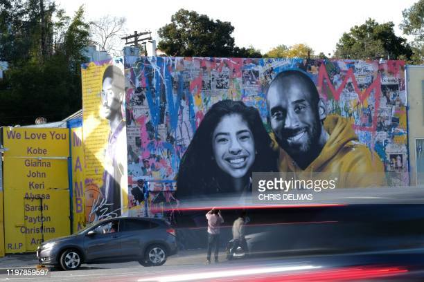 Cars drive by a new mural by French artist Mr. Brainwash picturing Kobe Bryant and his daughter Gigi is seen in Los Angeles on January 31, 2020. /...