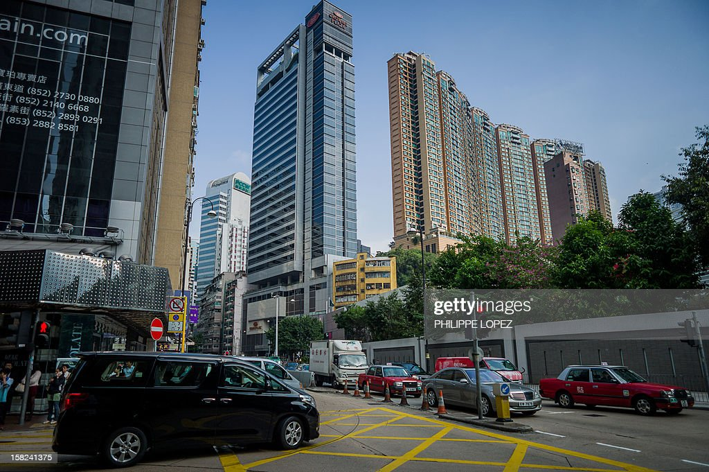 Cars drive by high rise buildings in Hong Kong on December 12, 2012. The International Monetary Fund warned that Hong Kong could see an abrupt fall in property prices after years of dramatic increases in one of the world's most expensive housing markets. AFP PHOTO / Philippe Lopez