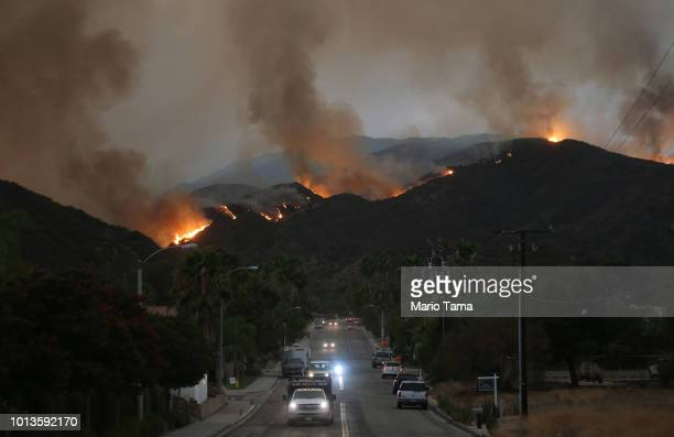 Cars drive down a hill in a mandatory evacuation area as the Holy Fire burns in Cleveland National Forest on August 8 2018 in Lake Elsinore...