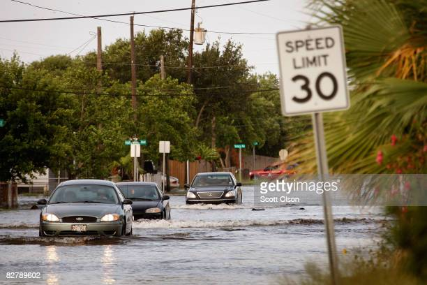 Cars drive down a street flooded by Hurricane Ike as water begins to rise in many areas September 12 2008 in Galveston Texas The eye of the hurricane...