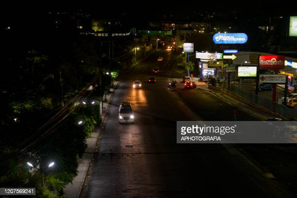 Cars drive down an empty road next to a shoping mall on March 17 2020 in San Salvador El Salvador Despite no cases of COVID19 have been confirmed in...