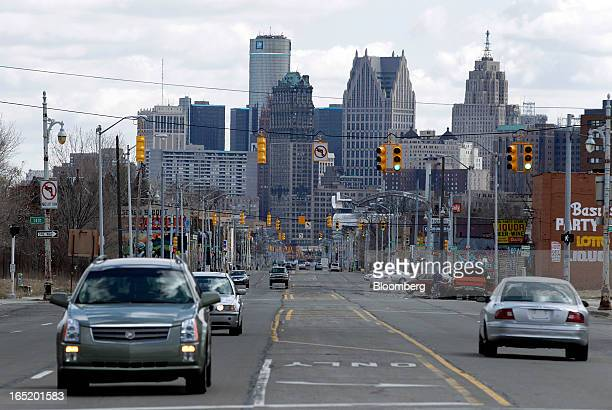 Cars drive down Grand River Avenue as the General Motors Co headquarters building stands in the skyline of Detroit Michigan US on Monday April 1 2013...