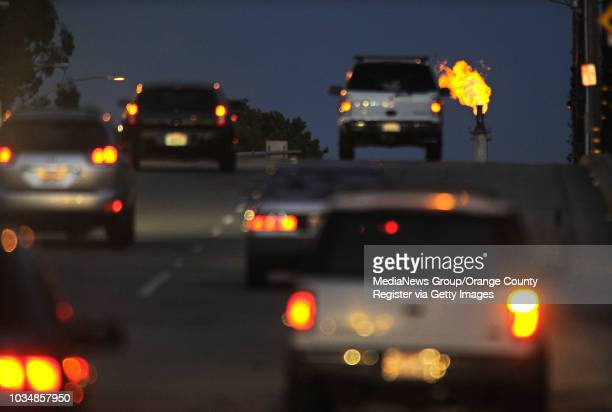 Cars drive east along Del Amo Boulevard in Torrance as a flare off of gas burns out of the stack at the ExxonMobil refinery Monday evening.