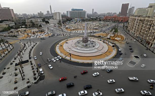 Cars drive in the Egyptian capital Cairo's Tahrir square, shortly before the first day of a two-weeks night-time curfew imposed by the authorities to...