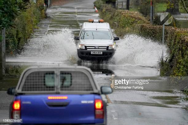 Cars drive on a flooded road as the River Conwy bursts its banks on October 30, 2020 in Llanrwst, Wales. Authorities have issued yellow weather...