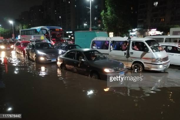 Cars drive on a flooded street following rainfall that led to traffic jam in the Heliopolis district in the Egyptian capital Cairo on October 22,...