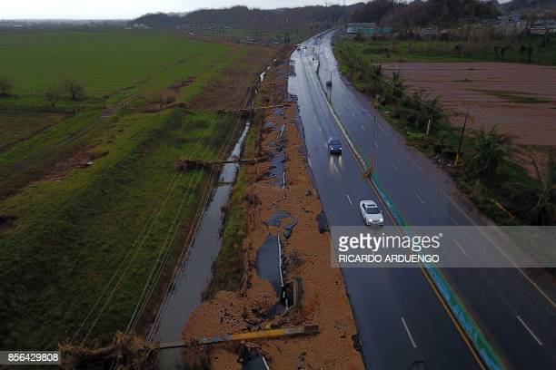 TOPSHOT Cars drive on a highway next to downed power line poles by Hurricane Maria in Vega Alta Puerto Rico on October 1 2017 President Donald Trump...