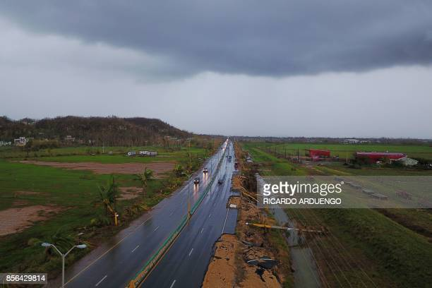 Cars drive on a highway next to downed power line poles by Hurricane Maria in Vega Alta Puerto Rico on October 1 2017 President Donald Trump on...