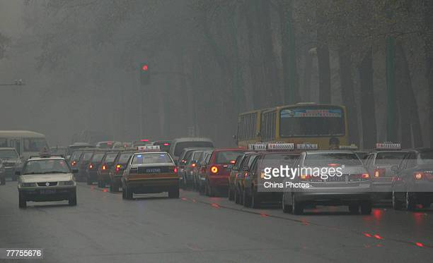 Cars drive on a street in heavy fog on November 7 2007 in Changchun of Jilin Province China Heavy fog enveloped the capital city of Jilin Province...
