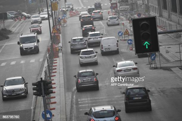 Cars drive on a street in Milan on October 20 as smog has reached alarming levels in northern Italy in recent days. Drivers in Milan will face a...