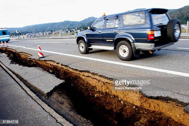 Cars drive on the partially collapsed Hokuriku highway October 24, 2004 in Ojiya, Niigata Prefecture, Japan. A series of powerful earthquakes, with...