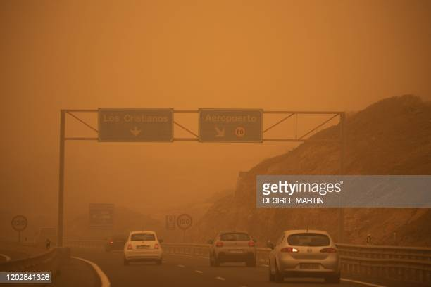 Cars drive on the TF-1 highway during a sandstorm in Santa Cruz de Tenerife, on the Canary Island of Tenerife, on February 23, 2020. - Airports on...