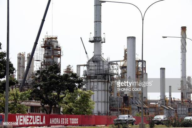 Cars drive pass in fornt of a oil refinery in the Venezuelan city of Moron on April 30 2009 The petroleum sector dominates Venezuela's mixed economy...
