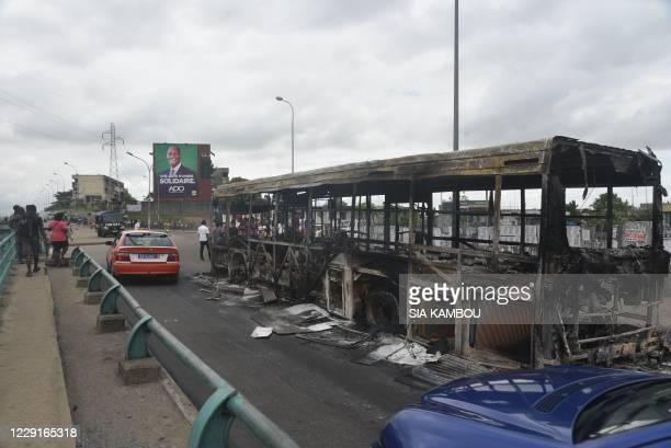 Cars drive past a burnt bus that was set alight during demonstrations against a third term of the outgoing Ivorian President Alassane Ouattara in the...
