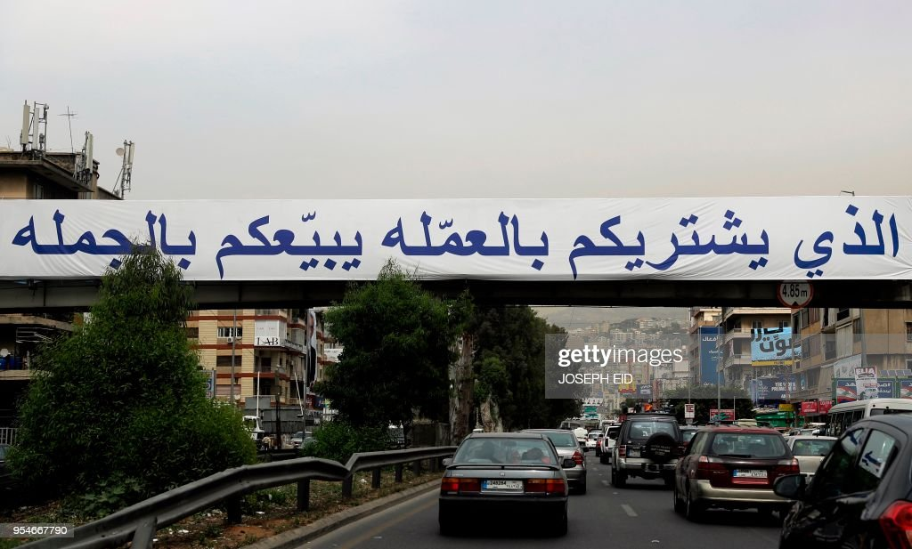 Cars drive past a huge banner which reads in Arabic: \'Those who buy ...