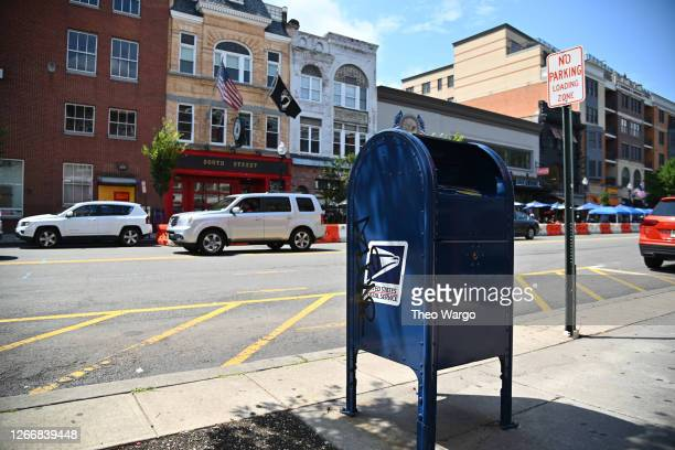 Cars drive past a mailbox on August 17, 2020 in Morristown, New Jersey. Postmaster General Louis DeJoy has accepted House Democrats' request to come...
