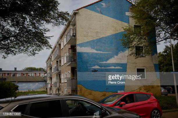Cars drive past a mural in a residential area near the Tata Steel plant on August 22, 2021 in Ijmuiden. The Tata steel plant is under investigation...