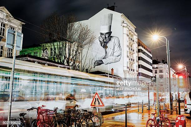 Cars drive past a mural of French chef Paul Bocuse painted on the side of a building in Lyon on December 21 2015 The mural was designed by artists...