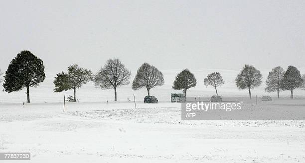 Cars drive past a row of trees in a snow covered landscape 10 November 2007 near Holzkirchen southern Germany as the state of Bavaria experiences...