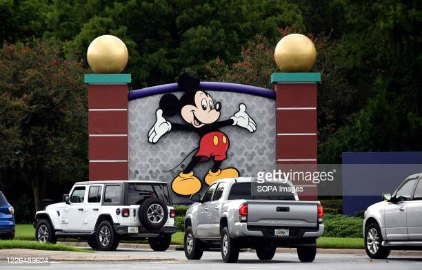 Cars drive past a sign featuring Mickey Mouse at the entrance to Walt Disney World on the day that portions of the theme park, including the Magic...