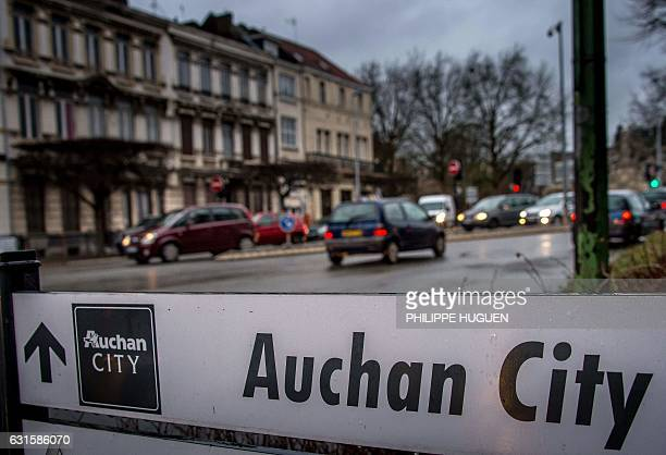 Cars drive past a sign for the Auchan City supermarket in Tourcoing northern France on January 12 2017 employees of Auchan City in Tourcoing where a...