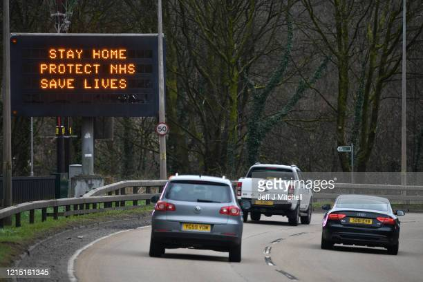Cars drive past a sign on the A82 north bound on March 27, 2020 in Glasgow, Scotland. First Minister of Scotland Nicola Sturgeon along with British...