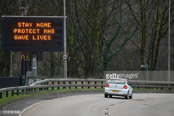 Cars drive past a sign on the A82 north bound on March 27 2020 in Glasgow Scotland First Minister of Scotland Nicola Sturgeon along with British...