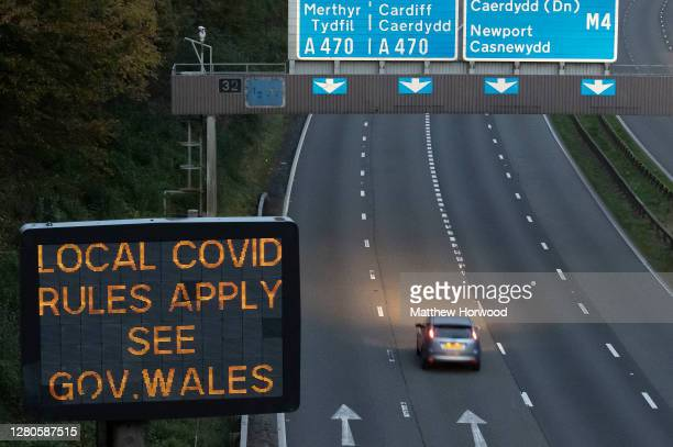 Cars drive past a sign on the M4 motorway which warns of local covid rules on October 16, 2020 in Cardiff, Wales. The Welsh First Minister Mark...