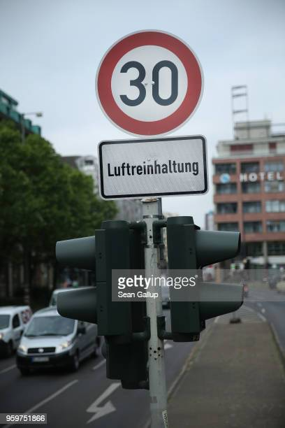 Cars drive past a speed limit sign of 30 kilometers per hour and a sign underneath that reads Air purity control on a test section of Leipziger...